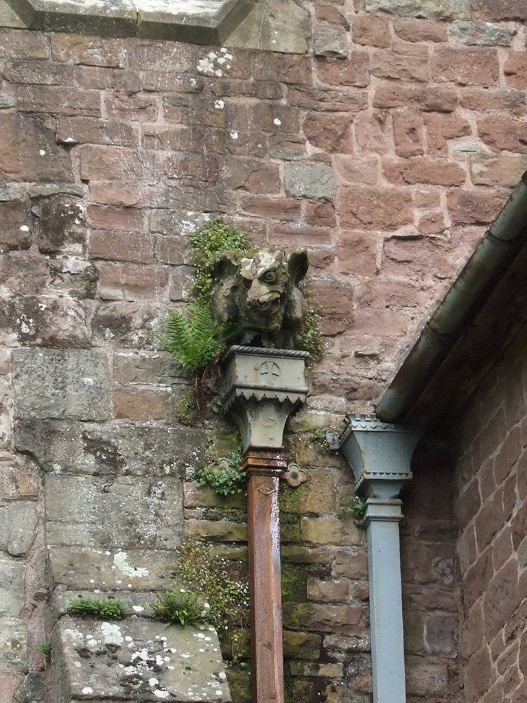 Vegetation growth around hopper head gargoyle